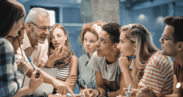 Teacher explains concept in huddle of students